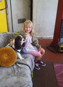 a little girl sitting smiling with her dog