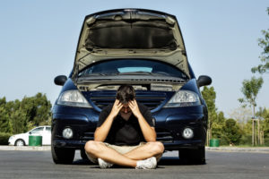 a young man sitting the pavement frustrated in front of his broken down car concerns with your car