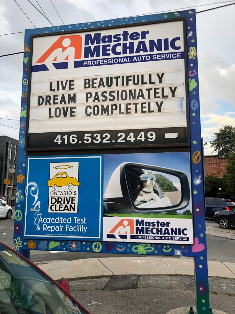 The store sign at Master Mechanic High Park with a positive quote: Live beautifully, dream passionately, love completely.